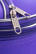 Pull Tab and Chain of a Zipper on a Violet Suitcase - stock photo