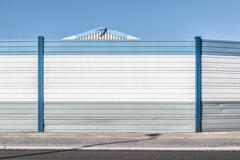 Corrugated wall by road against clear blue sky Stock Photos