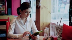 A woman surfing the internet in cafe Stock Footage