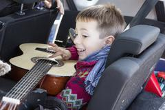 Side view of happy boy playing guitar in car - stock photo