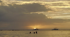 Philippines - Children silhouetted by sunset playing in water - stock footage