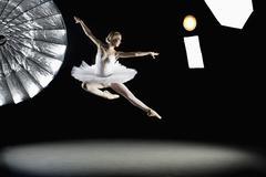 Full length of ballerina performing in mid-air at studio - stock photo