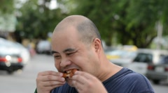 Fat Asian Thai man eating fried chicken drumstick greedily with hunger gluttony Stock Footage