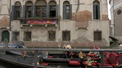 Gondolier tying together two gondolas and taking pictures of a couple in Venice Stock Footage