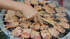 Sticks of skewer pork food cooked on the grill in Thai outdoor market restaurant Stock Footage