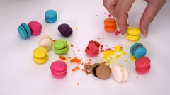 Woman hand picking up messy colorful macaroon candy dessert and smash it - stock footage