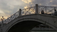 People walking on one of the Venetian bridges at evening in Venice - stock footage