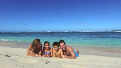 Family laying on a sandy beach - stock footage