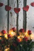 Stock Photo of Valentine: Heart Banner Above Red Roses And Light Bulbs
