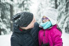 Stock Photo of Father and daughter enjoying snow at daytime