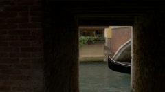 Gondola with tourists taking pictures navigating  from under a bridge in Venice - stock footage