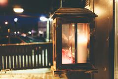 Burning candle in a glass box on the street before an institution at night - stock photo