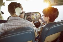 Rear view of father and son in cockpit of private airplane Stock Photos
