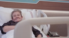 Grand children hug their grandmother in hospital room Stock Footage