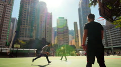 Young athletes play basket ball on public playground in Hong Kong downtown Stock Footage