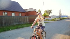Drunken man cycling fast along country road in slowmotion at beautiful sunset Stock Footage