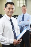 Young Businessman With Senior Mentor In Office Stock Photos