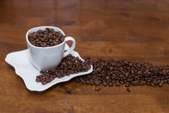 A scattering of coffee beans white cup and saucer Stock Photos