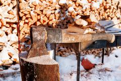 Axe in a wooden deck. Winter sunny day. Rural background with folded pile of - stock photo