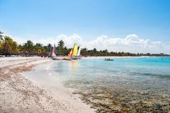 Sea coast - white sand, bathing people, sailing vessels, bright palm-trees. V Kuvituskuvat