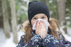 Child with tissue outside in forest winter season Stock Photos