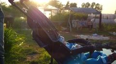 Stock Video Footage of Mom cradles a baby  in a stroller at the garden pond in slowmotion during
