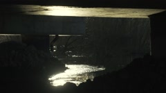 Lit by the rising river passes under the concrete bridge in slow motion Stock Footage