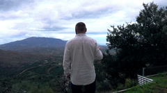 Young man holding glass of wine and admire view in country, super slow motion - stock footage