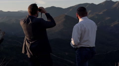 Businessman with binoculars showing his partner something in country mountains Stock Footage
