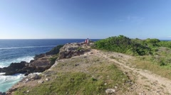 Drone view of hikers looking at scenery from cliff Stock Footage