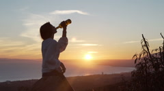Silhouette of happy woman drinking wine during sunset in the country Stock Footage