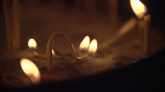 Curved candle burns in the sand Stock Footage
