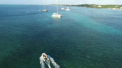 AERIAL: White Inflatable Boat Cruising By Sailboats - stock footage
