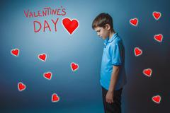 Adolescence boy lowered his head is Valentine's Day celebration Stock Photos