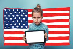 adolescence girl holding a tablet frowned American flag USA - stock photo