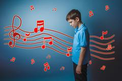 Adolescent boy lowered his head to prevent the sheet music sketc Stock Photos