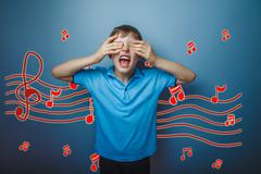 Adolescent boy screaming with his eyes closed hands music notes Stock Photos