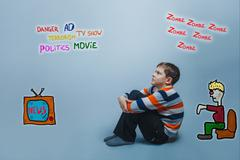 Adolescent boy sitting looking up media influence zombies tv new Stock Photos