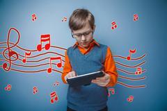 Adolescent boy working on a tablet retro music notes sketch prev Stock Photos
