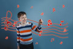 Adolescent the boy laughing holds fingers music notes sketch pre Stock Photos