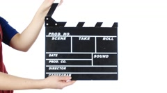 Girl uses movie production clapper board, on white Stock Footage