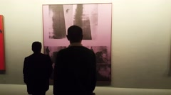 People looking at a painting by Andy Warhol in Tehran museum of contemporary art - stock footage
