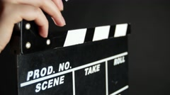 Stock Video Footage of Hands holding a film clapper board, on black, close up