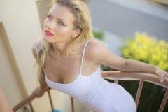 Stock Photo of Desire, beautiful blond woman in lingerie on the staircase of a terrace in su