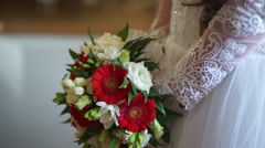 Bridal bouquet of red and white flowers in hands of the bride - stock footage