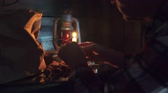 Cowboy eating walnuts by candlelight, red lantern, Stock Footage