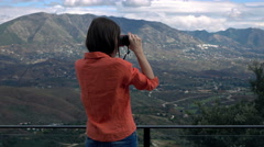 Young woman with binoculars admire view in country Stock Footage