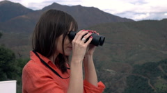 Frightened woman with binoculars watching view in country Stock Footage