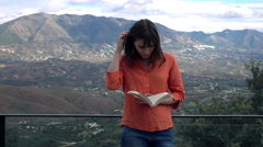 Young woman reading book standing on terrace Stock Footage