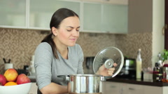 Beautiful young woman cooking and smelling the nice aromas from her meal HD Stock Footage